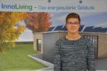 Der duale Student steht vor einem Plakat des energieautarken Gebäude.