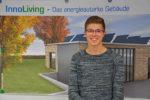 Der duale Student steht lächelnd vor einem Plakat des energieautarken Gebäude.