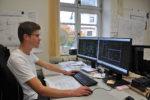 Ein dualer Student sitzt an seinem Computer und arbeitet mit einem Bauzeichenprogramm.